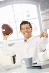 Cheerful businessman throwing football