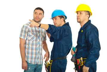 Builder team pointing away to a casual man