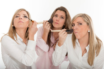 Three girls applying make-up