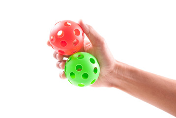 Hand Holding Red and Green Whistling Balls