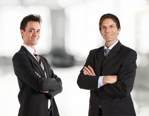 Two businessmen smiling. Soft background.