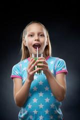 Little girl drinking juice, studio shot