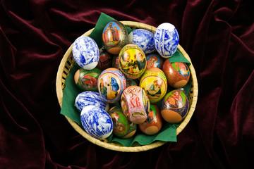 Easter eggs in straw dish on red velvet