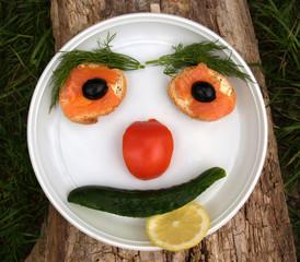 Пища на тарелка в виде лица человека