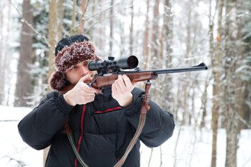 Hunter in a fur cap with ear flaps with sniper rifle in winter f