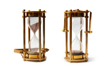 Golden hourglasses isolated over white