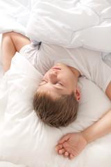 A boy sleeping under sunligth