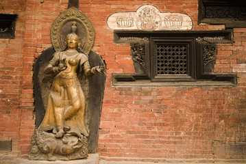 Bronze Deity at wall in Nepal temple 2.