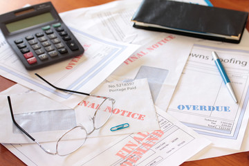 """""""Overdue Unpaid Bills on Table with Calculator and Cheque Book"""