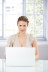 Young woman working on laptop at home smiling