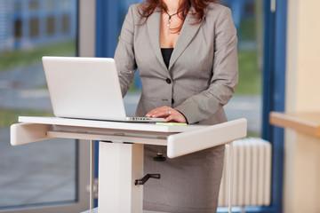 businessfrau am stehpult mit laptop