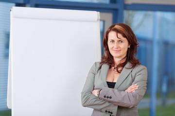lächelnde businessfrau steht neben dem flipchart