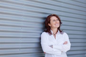 lachende businessfrau lehnt an der wand