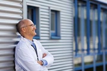 lächelnder arzt vor der klinik