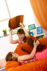 Small girls having fun in pillow fight