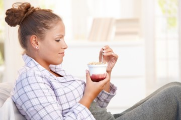 Attractive young woman eating yoghurt in bed