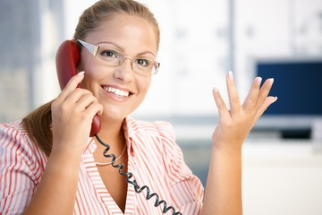Attractive woman on the phone in office smiling