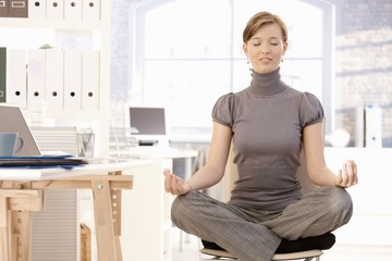 Attractive office worker practicing yoga