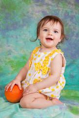 little girl with the orange on the floor in studio