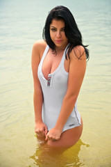 sexy seductive young brunette in wet shirt on beach water