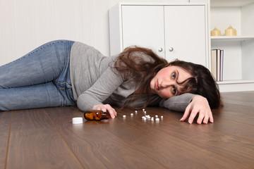 Depressed teenage girl lying on floor with pills