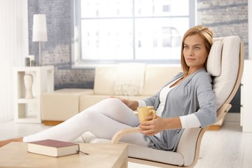 Attractive woman in armchair with coffee mug