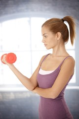 Sporty woman exercising with dumbbell