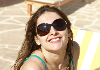 Beautiful Girl with long hair in big brown glasses sunbathing