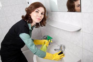 Frau putzt Waschbecken