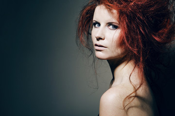 Young fashion model with curly red hair.