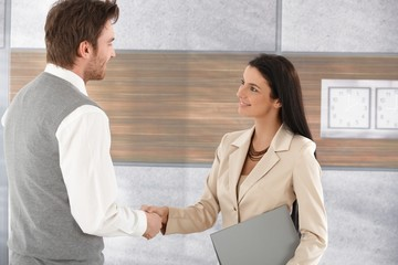 Young businesspeople shaking hands smiling