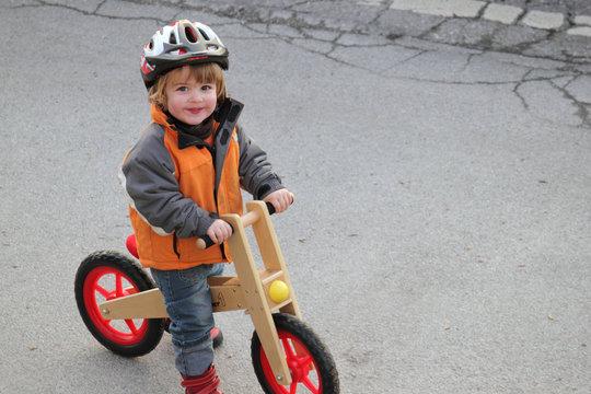 Kleiner Junge mit Helm auf dem Laufrad