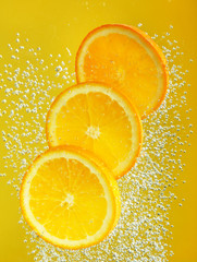 Fresh orange dropped into water