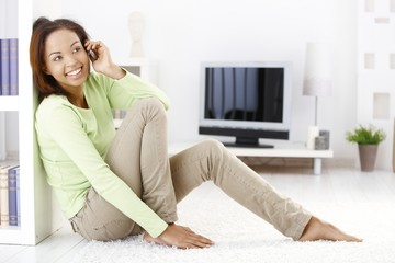Cheerful woman calling in living room