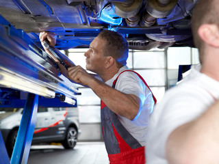 Motorcar mechanic fixing the engine of a car in a garage