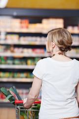 frau schiebt einkaufswagen durch den supermarkt