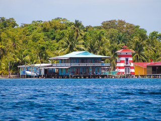 Stilt house over the sea with a lighthouse and tropical vegetation, Caribbean, Bocas del toro, Carenero island, Panama