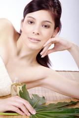 Beauty Frau liegt mit Massage Öl Flasche und blickt hübsch