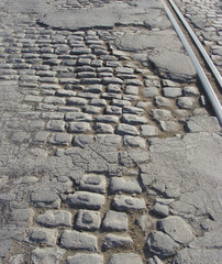very old road with damaged asphalt , cobble-stone and tram-rails