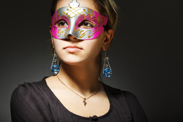 Portrait of beautiful young woman wearing carnival mask