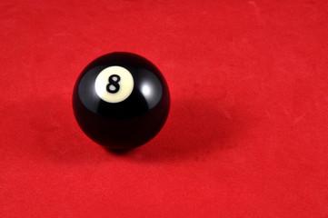 Schwarze Billardkugel auf rotem Samt