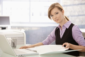 Office worker doing paperwork at desk