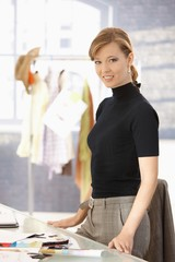 Young attractive female fashion designer working