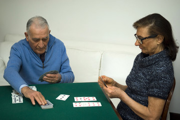 Elderly couple playing a game of cards  at home