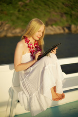 Girl with tablet PC on ship at sunset