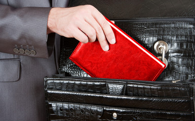 Fotobehang - Hand taking red organizer from briefcase