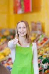 verkäuferin in einzelhandel zeigt daumen hoch