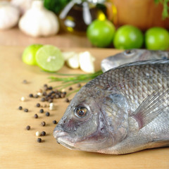 Raw fish called Tilapia surrounded by seasoning