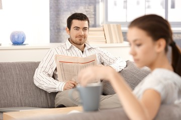 Young couple sitting in living room on sofa