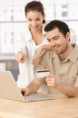 Happy couple shopping online having fun smiling